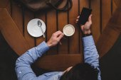 man with coffee using smartphone