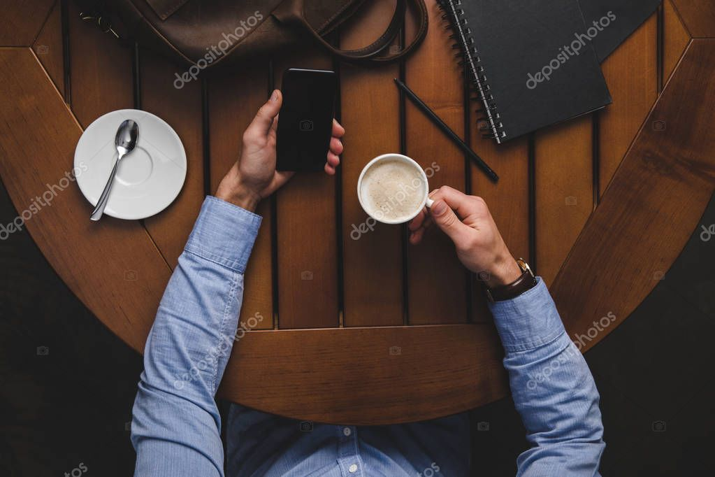 man with smartphone drinking coffee