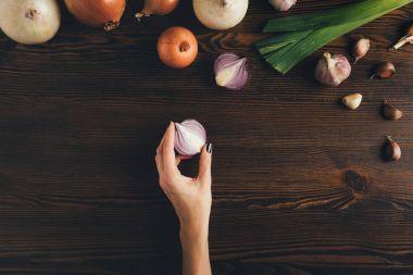 woman holding half of onion