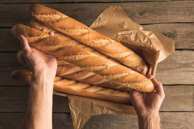 hands holding box with baguettes