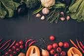 Photo top view of colored ripe vegetables on gray tabletop