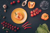 top view of bell peppers and cherry tomatoes on gray table