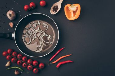 Top view of frying pan with onion and oil among vegetables on gray table stock vector