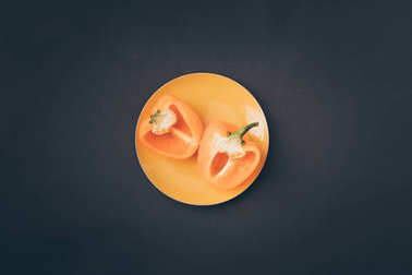 top view of two halves of yellow bell pepper on yellow plate on gray