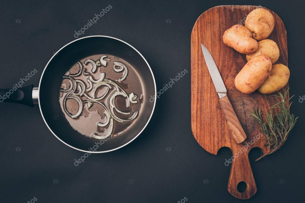 top view of frying pan with onion and wooden board with potatoes on gray surface