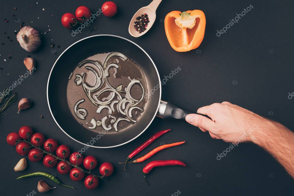 cropped image of man holding frying pan above gray table
