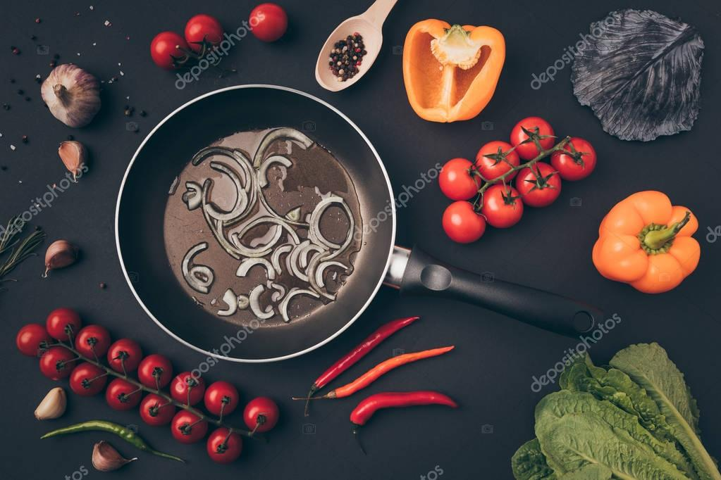 top view of frying pan with onion among vegetables on gray table