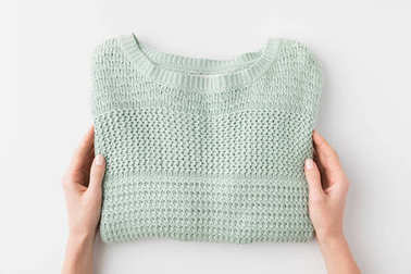 hands with stylish knitted sweater