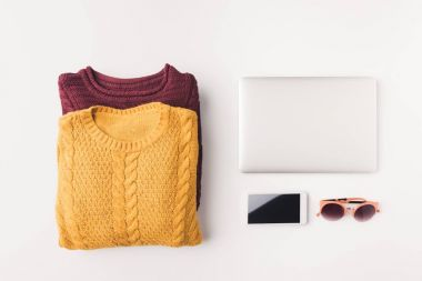 Flat lay with knitted sweaters, sunglasses, laptop, smartphone, isolated on white stock vector