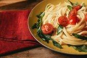 Detailní záběr z tradiční italské těstoviny s rajčaty a rukolou v desce