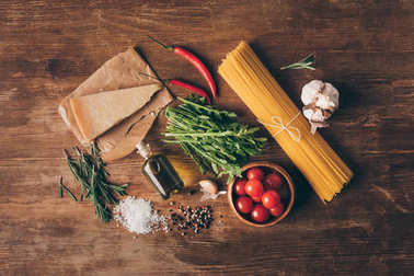 top view of traditional row pasta and fresh ingredients on wooden tabletop