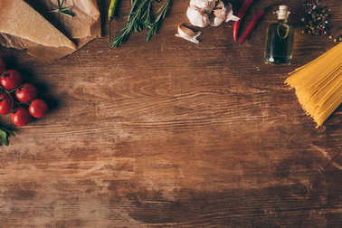 top view of row pasta and fresh ingredients on wooden table with copy space
