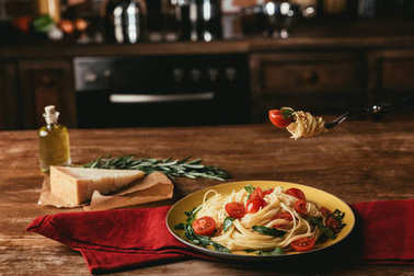 delicious italian pasta with tomatoes and arugula in plate on table with Parmesan and rosemary