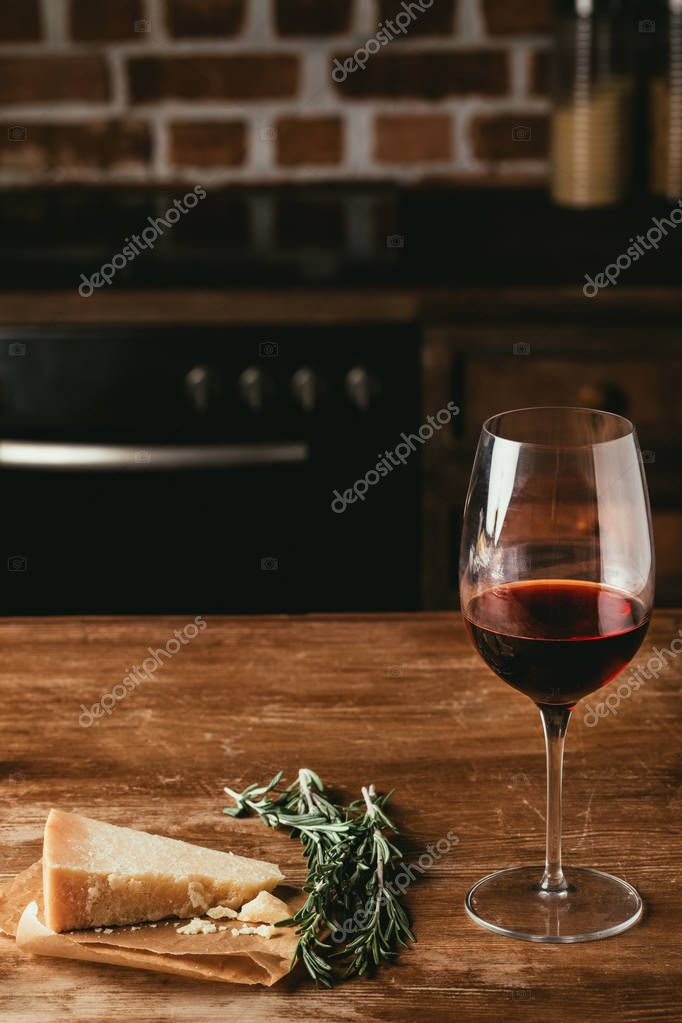 glass of red wine, Parmesan cheese and fresh rosemary on wooden tabletop in kitchen