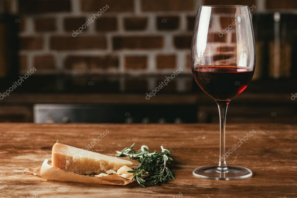 glass of red wine, Parmesan cheese and fresh rosemary on wooden tabletop