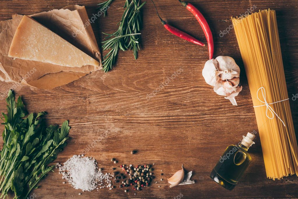 top view of row pasta and fresh ingredients on wooden tabletop with copy space