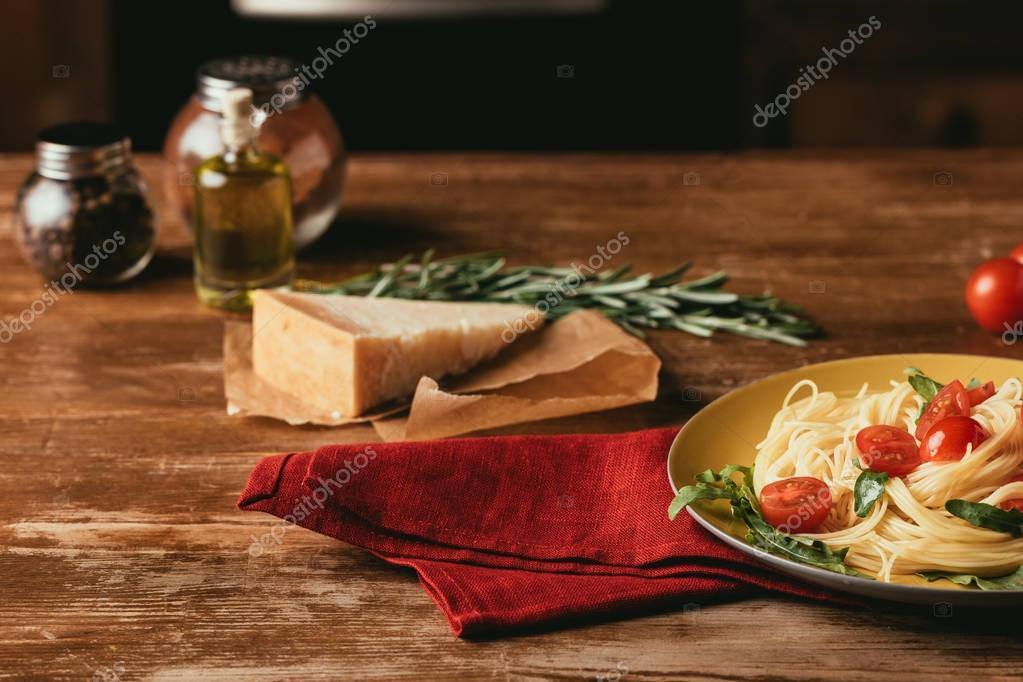 traditional italian pasta with tomatoes and arugula in plate on wooden table with Parmesan, rosemary and oil