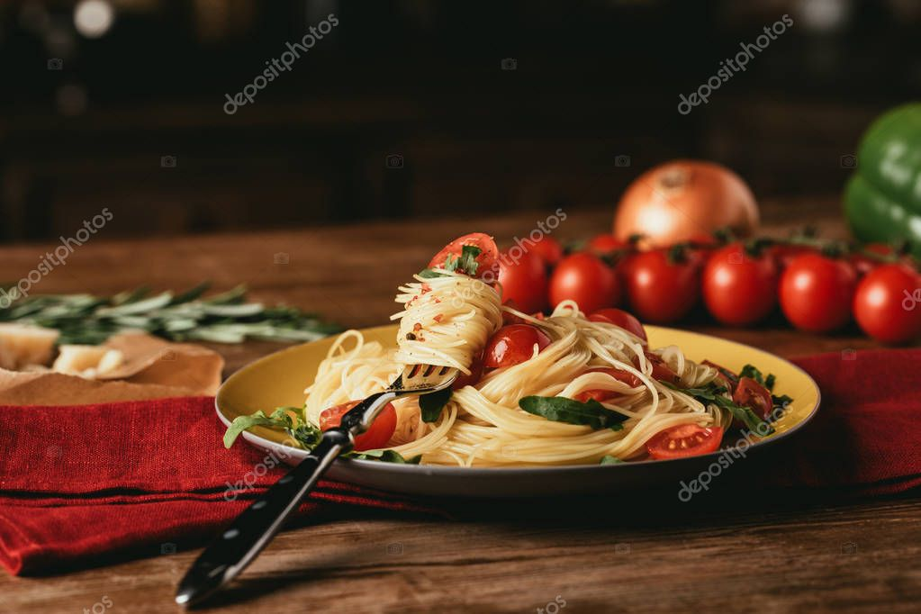traditional italian pasta with tomatoes and arugula in plate with fork