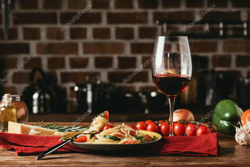 traditional italian pasta with tomatoes and arugula in plate and glass of red wine