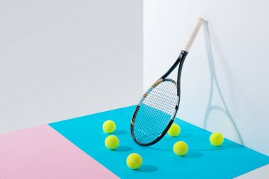 yellow tennis balls on blue and pink papers and tennis racket at white wall
