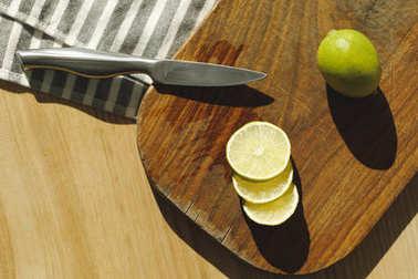 top view of limes and knife on wooden board on table