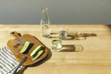 cut cucumbers on wooden board and mineral water on wooden tabletop