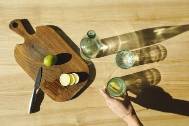 cropped image of woman putting glass with lemonade on wooden table