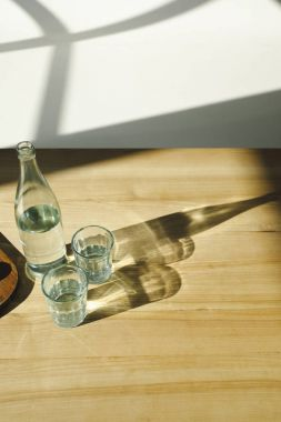 overhead view of transparent bottle and glasses with mineral water