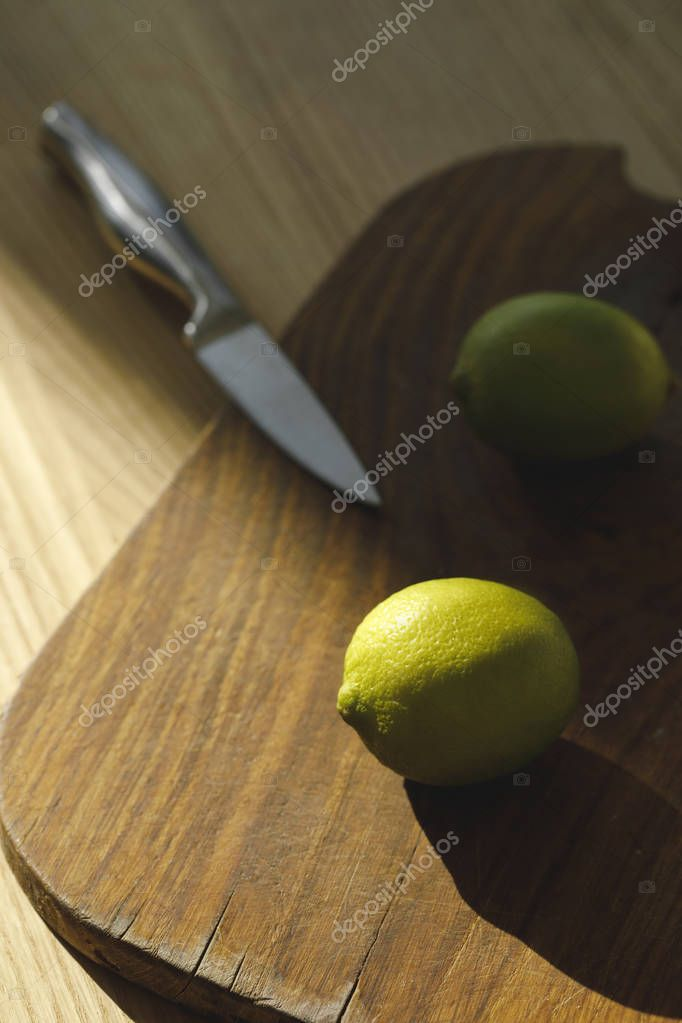 overhead view of limes and knife on wooden board on tabletop