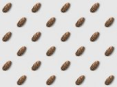 repetitive pattern of pine cones on white surface