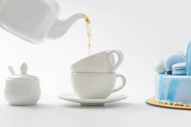 teapot pouring tea in cups near blue cake isolated on white