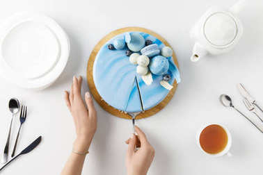 top view of cropped hands slicing cake on chopping board isolated on white