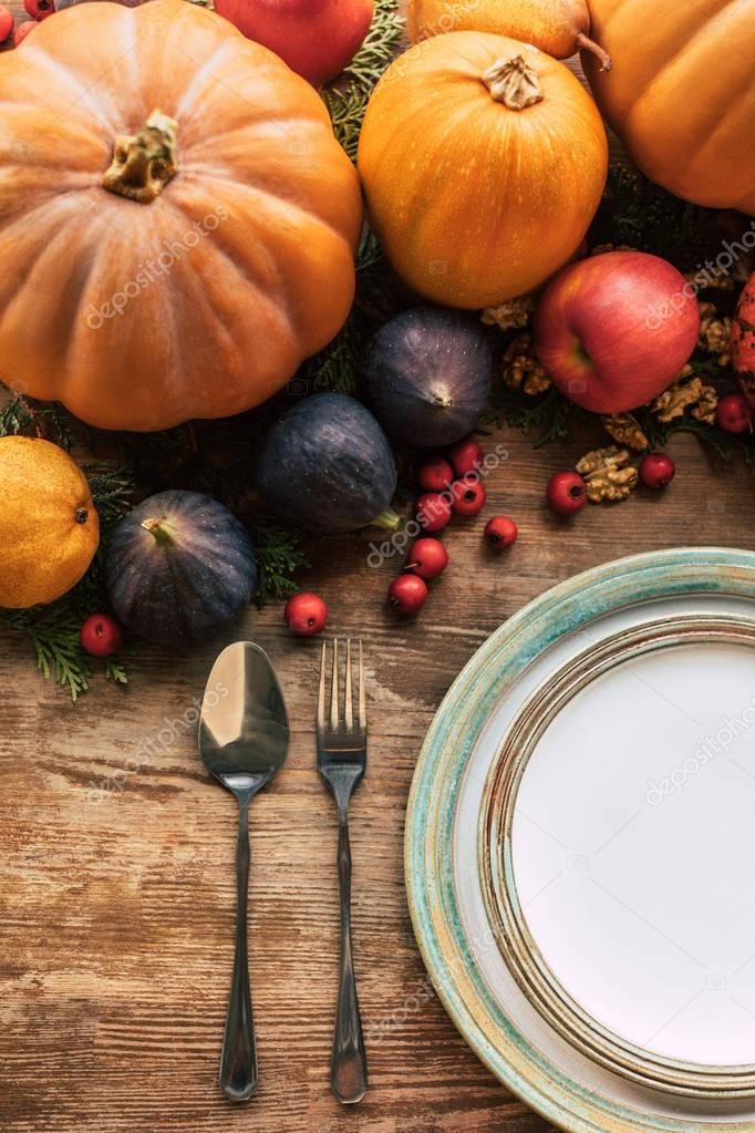 top view of table setting with various fruits and pumpkins as christmas decor