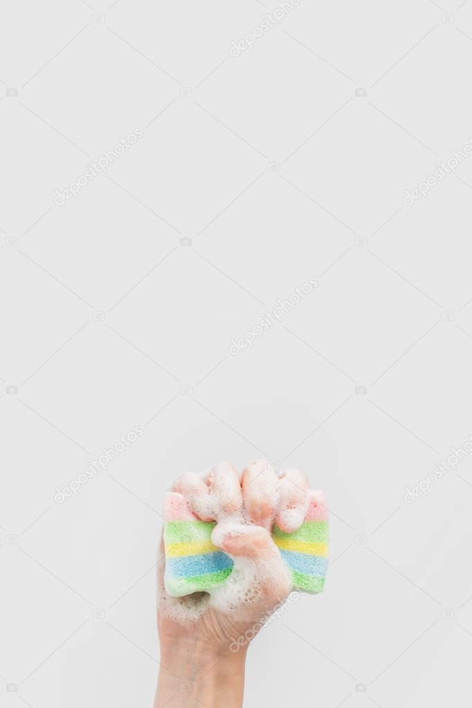 cropped view of hand holding washing sponge with foam, isolated on white