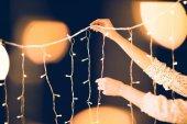 ritagliata colpo della donna appeso bella ghirlanda di Natale su priorità bassa nera