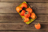 top view of persimmons on yellow bowl on striped wooden table