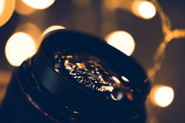 close-up shot of christmas lights reflecting in glass of camera lens