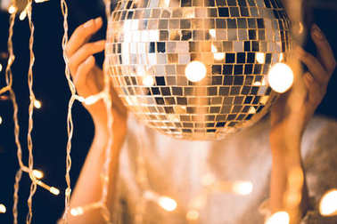 close-up shot of woman touching disco ball with beautiful garlands around