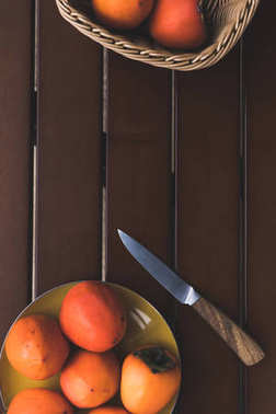 top view of straw basket and plate with persimmons and knife on brown table