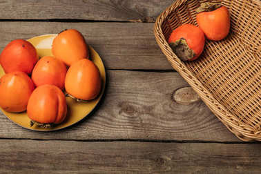 ripe persimmons on plate and in straw basket