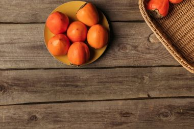 top view of appetizing persimmons on plate and in basket on table