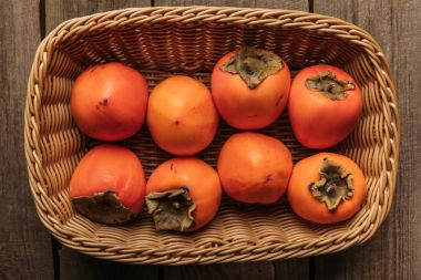 top view of appetizing persimmons in straw basket on table