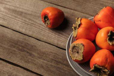 ripe orange persimmons on gray wooden table