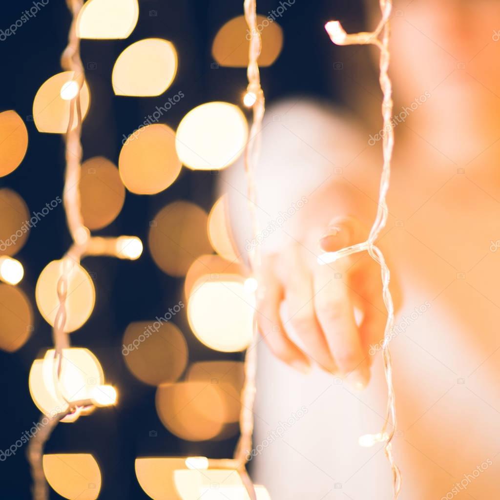 cropped shot of woman pointing at camera behind holiday garland