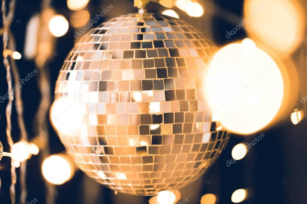 golden glossy disco ball with christmas lights around