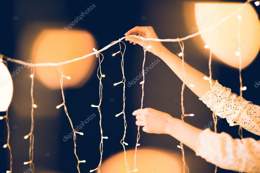 cropped shot of woman hanging beautiful christmas garland on black background