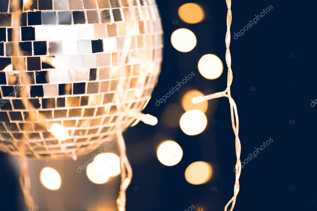 close-up shot of disco ball with garland on black background