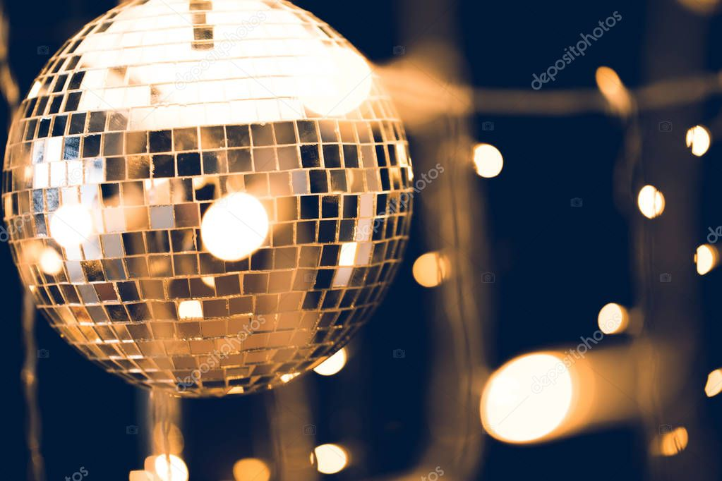 glossy disco ball with beautiful garland on foreground