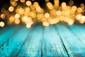Fotografie festive bokeh lights on blue wooden surface, christmas background