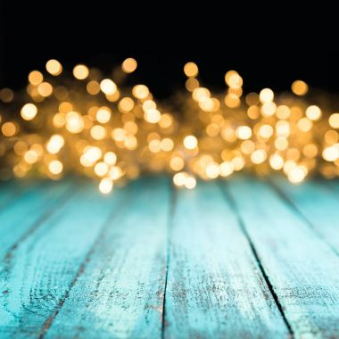 decorative bokeh lights on blue wooden surface, christmas background